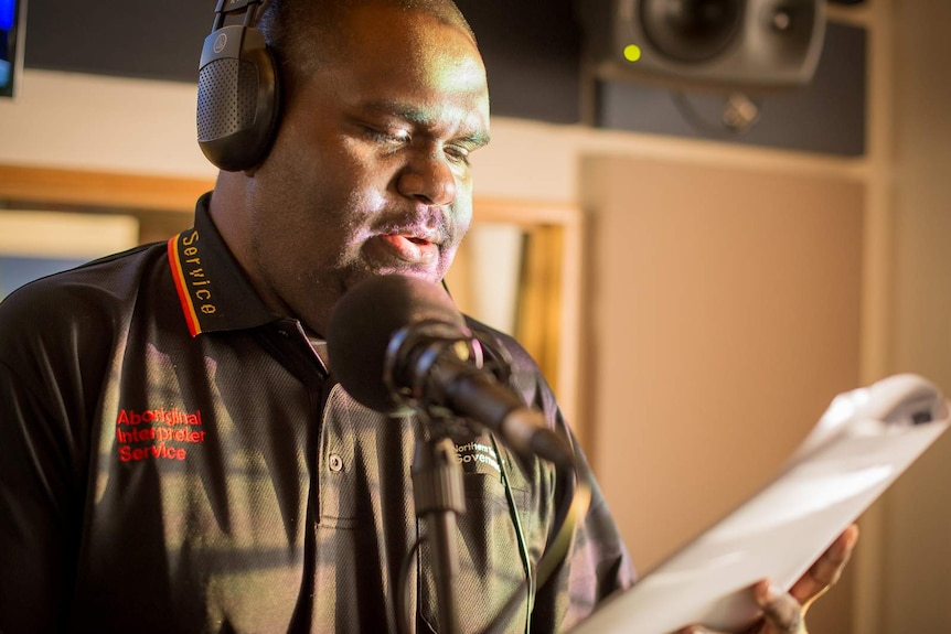 An Indigenous man reads from a script as he translates the news into language inside a radio broadcasting studio.