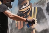 A man wearing breathing protection spraypaints a mural on a wall.