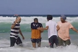 Four men, two of whom are wearing turbans, stand knee-deep in the ocean as the surf rolls in.