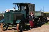 A lady in a black jumper and red skirt stands in front of a dark green truck with two trailers made of wood.