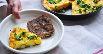 A slice of frittata in a bowl with bread alongside a pan of frittata, perfect for a weekend brunch.