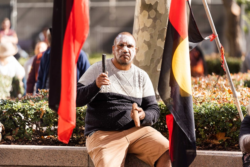A man sits between two Aboriginal flags, wearing white face paint, banging two wooden sticks — traditional instruments.