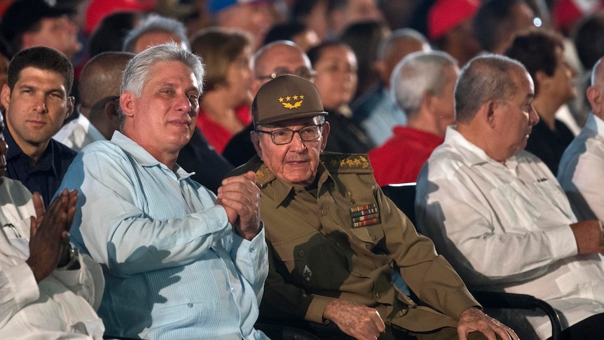Castro and Diaz-Canel sitting in an audience together.