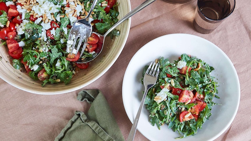 Lentil, rocket and pesto salad with feta cheese and cherry tomatoes in two bowls on a table setting.