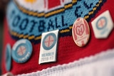 Membership pins for Melbourne City FC are pinned to a Melbourne City scarf.