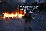 """A protester wearing black holds a sign saying """"capitalism kills"""" in front of a fire."""