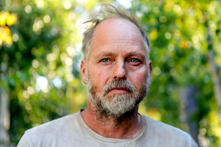 Man with thinning grey hair and a greyish beard looks into distance with trees behind