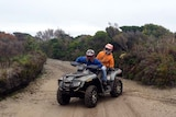 Two people ride a quad bike on a track on Tasmania's west coast.