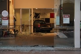 The car is lodged in the back wall of the bank, surrounded by broken glass and emergency tape.