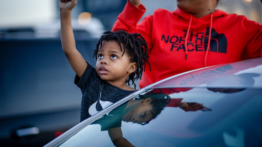 A small black boy raises his fist next to a car