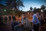 A woman in veil holds a prayer mat in a street at dusk as soldiers look on
