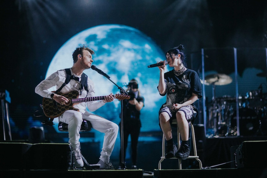 A scene from the documentary  Billie Eilish: The World's a Little Blurry with Billie and her brother Finneas performing on stage