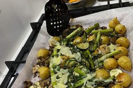 Potato, asparagus and cheese line an oven tray.
