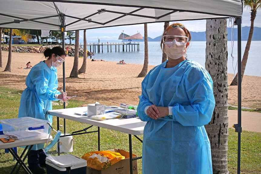 Two nurses in protective coverings and face masks work inside a temporary tent erected on the foreshore of Townsville's Strand