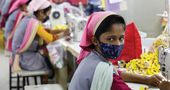 Female Bangladeshi garment maker sewing clothes and wearing a face mask.
