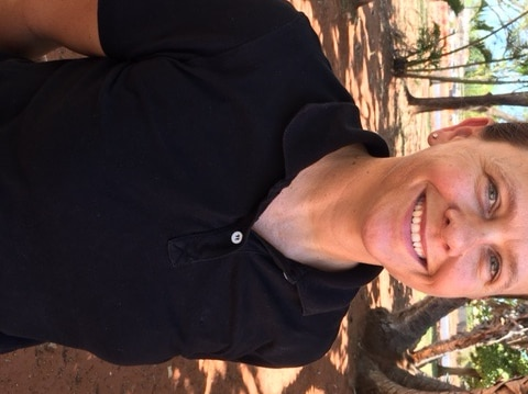 Female police officer standing with trees in the background