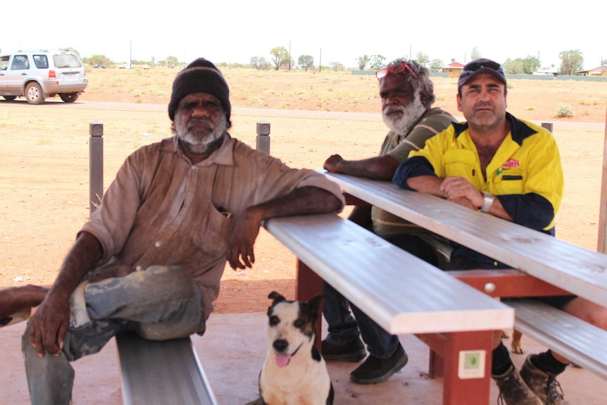 Three men sitting at a public bench with a dog