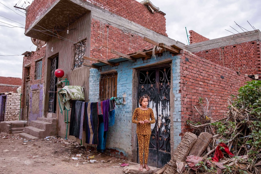 A little girl in pyjamas stands outside her home looking solemn