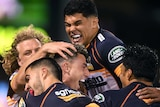 The Brumbies Super Rugby AU players embrace as they celebrate a try against the Queensland Reds.