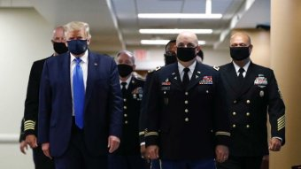 Donald Trump wearing a face mask walking next to military generals.