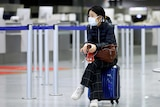 A young woman in a face mask sits on her suitcase at an airport
