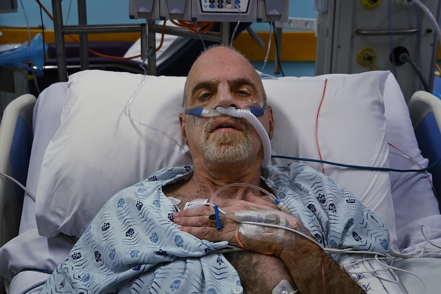 A man looks at the camera from his hospital bed.