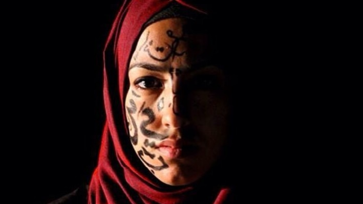 A woman wearing a red hijab with arabic letters on one side of her face, the other in darkness.