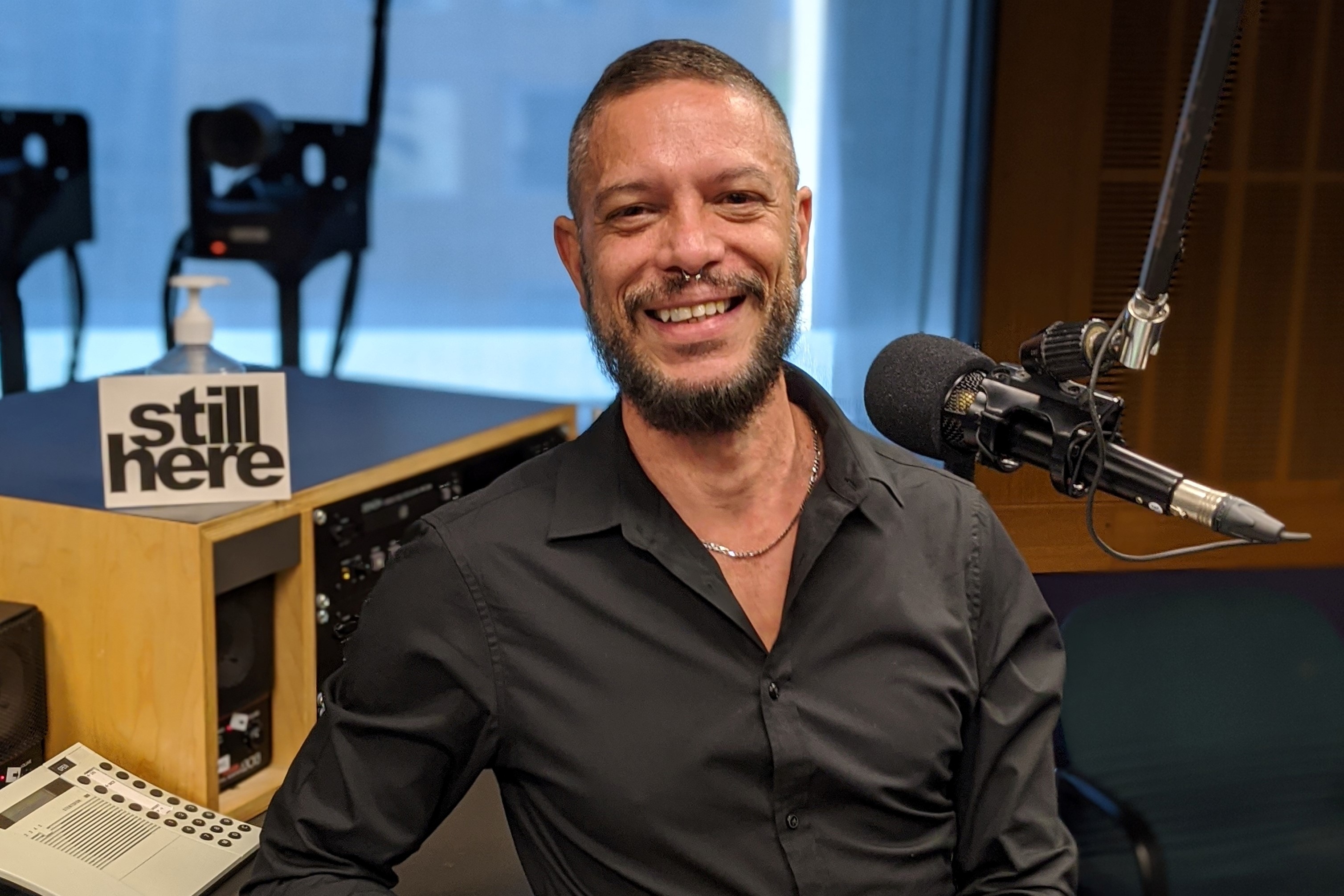 An Aboriginal man in his late 40s in a black shirt sitting in a radio studio and smiling