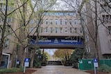 Part of the University of Melbourne campus. There are a lot of trees, and there is a blue welcome sign.