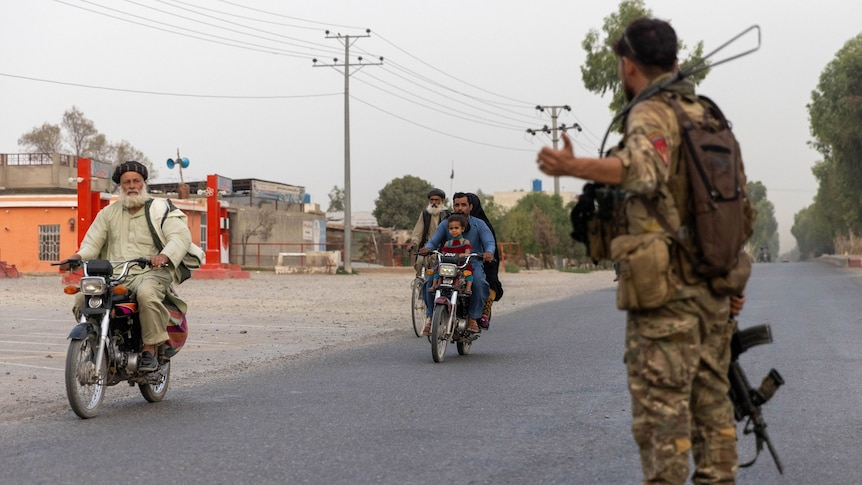 An Afghan solider directs people on motorbikes riding past on a road.