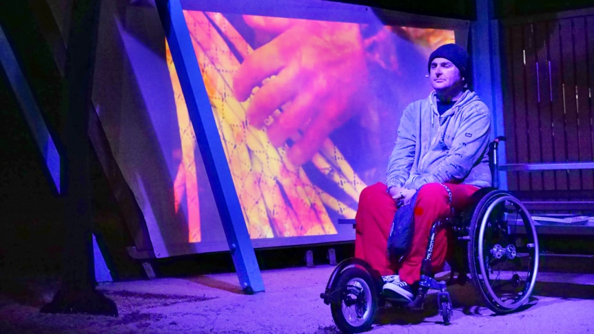 a man in a wheelchair sits in a barbecue shelter, illuminated by blue light and there's an image of a hand behind him