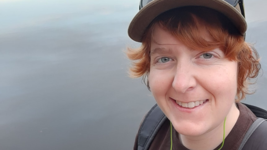 Woman wearing cap standing in front of a lake, for a story about challenges in seeking a hysterectomy.