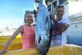 A couple poses with a big tuna.