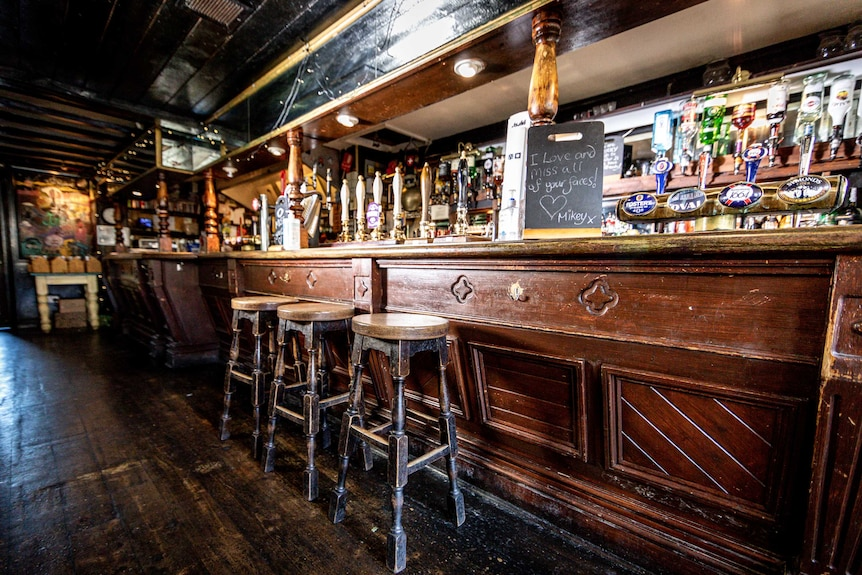 """An empty British pub with a sign reading """"I love and miss all your faces!"""""""