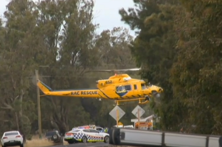 The yellow RAC rescue helicopter attends the scene of a crash on a country highway