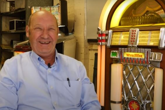 An elderly man in a blue shirt laughs as he sits by a jukebox