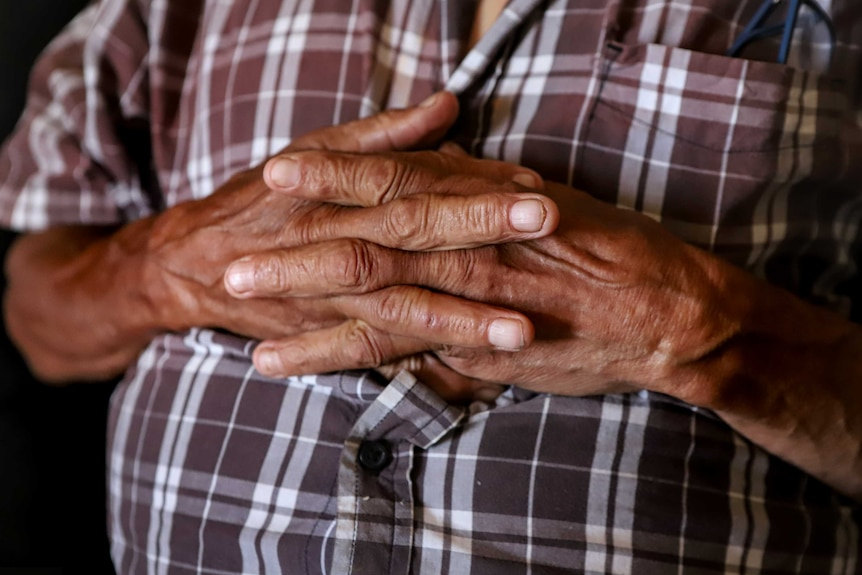 An Aboriginal man's hands interlocked resting on his chest, wearing a chequered shirt