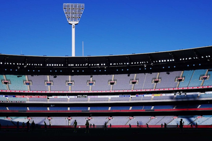 The afternoon sun hits the stands of an empty MCG stadium with players on the ground in silhouette.