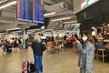 An airport with people wearing masks.