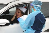 A woman wearing a Santa hat is tested for COVID-19 at a drive-through clinic in Bondi Beach on Christmas Day.