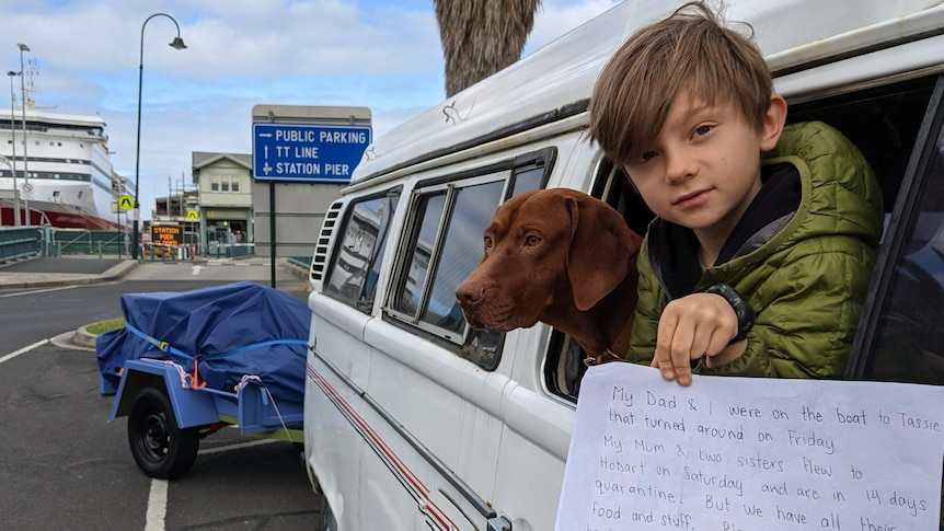 A little boy in green jacket holds white sign out of white van with brown dog in window behind him