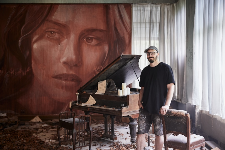 A man leans against a chair in a room filled with autumn leaves and a broken-down grand piano, with a mural of a woman's face.