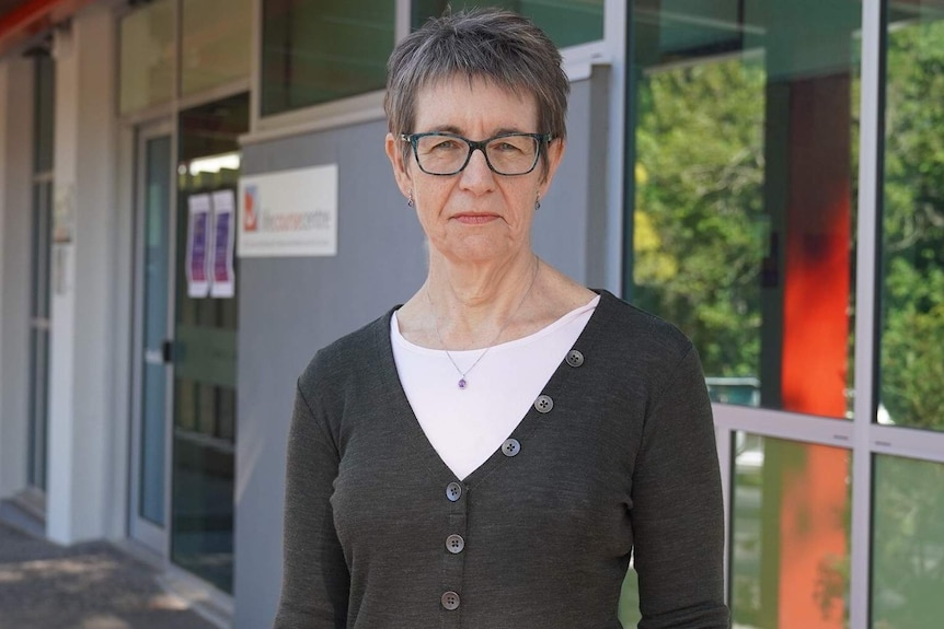 An older woman with glasses in front of a building.