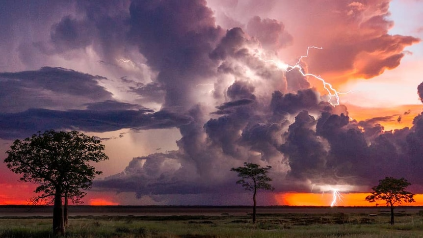 A thunderstorm rolls across a red sky in the country.