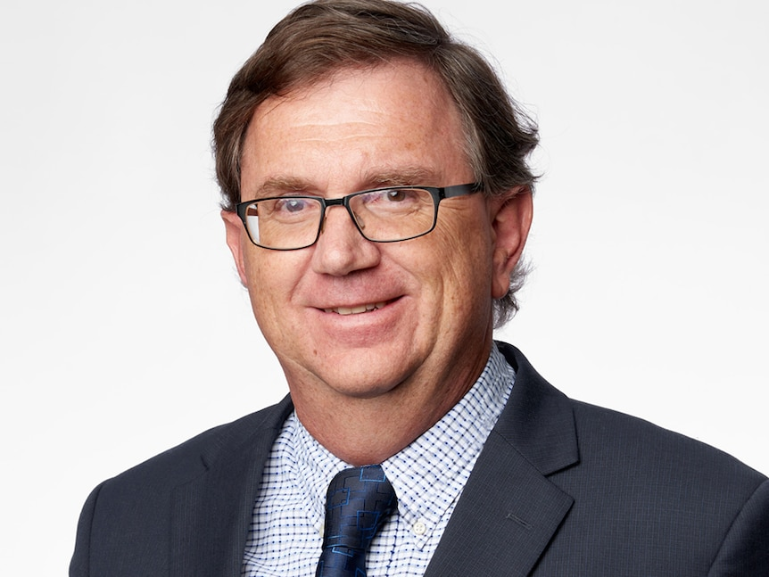 A corporate headshot of bespectacled man with dark hair, smiling and wearing a suit.