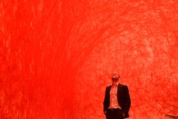 A man in a dark suit stands in an orange room staring up at the ceiling.