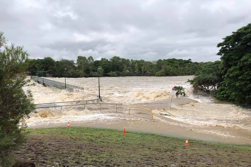 Floodwaters flow fast over Aplin's Weir in Mundingburra near Townsville on February 3, 2019.