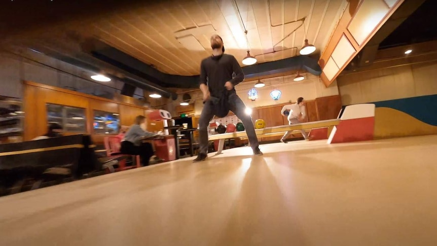 A man cleans a bowling ball in a bowling alley.