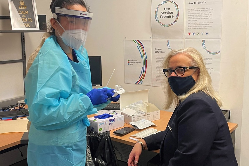 A woman sits in an office, getting prepared to be swabbed by a woman in protective clothing.