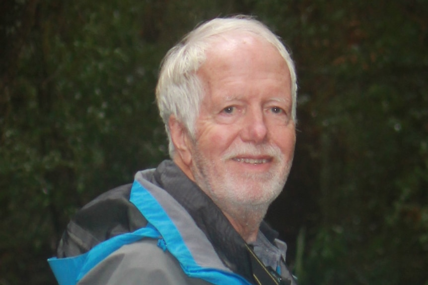 Photograph of a man with white hair and a beard smiling and wearing a rain jacket